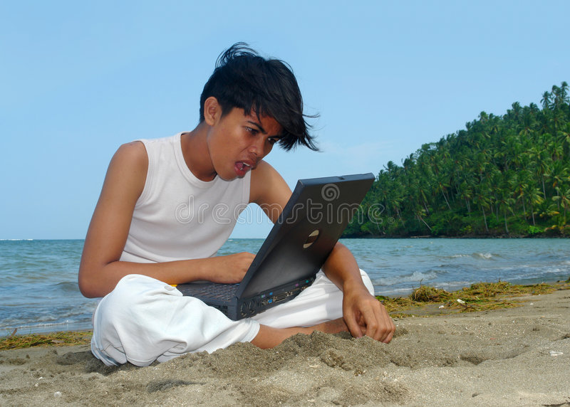 Surprising laptop on the beach. Asian boy with laptop computer on tropical pristine beach utterly amazed at technology and surprised what to learn. Concept of stock photo