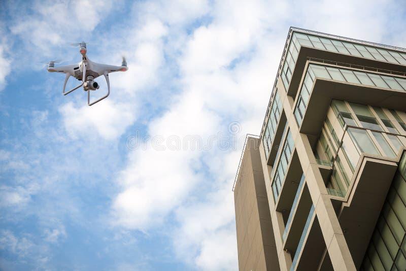 Surr med högt flyg för digital kamera för upplösning över stad En flyg- sikt av en flygamång--helikopter med lyftta landa kugghju arkivfoto