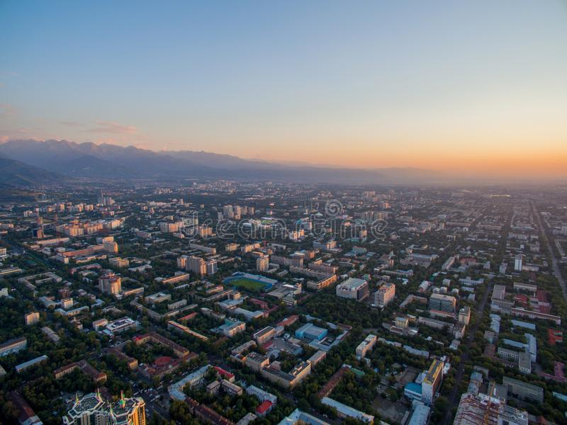 Surrbild över stad på solnedgången med berg arkivbild