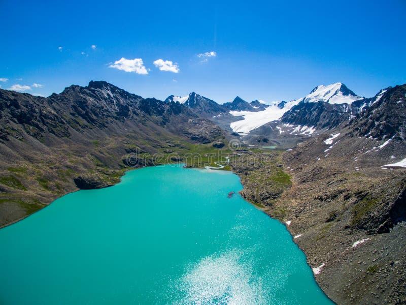 Surrbild från berg sjön med snö- och blåttSkyfrom berg sjön med snö och blå himmel arkivfoto
