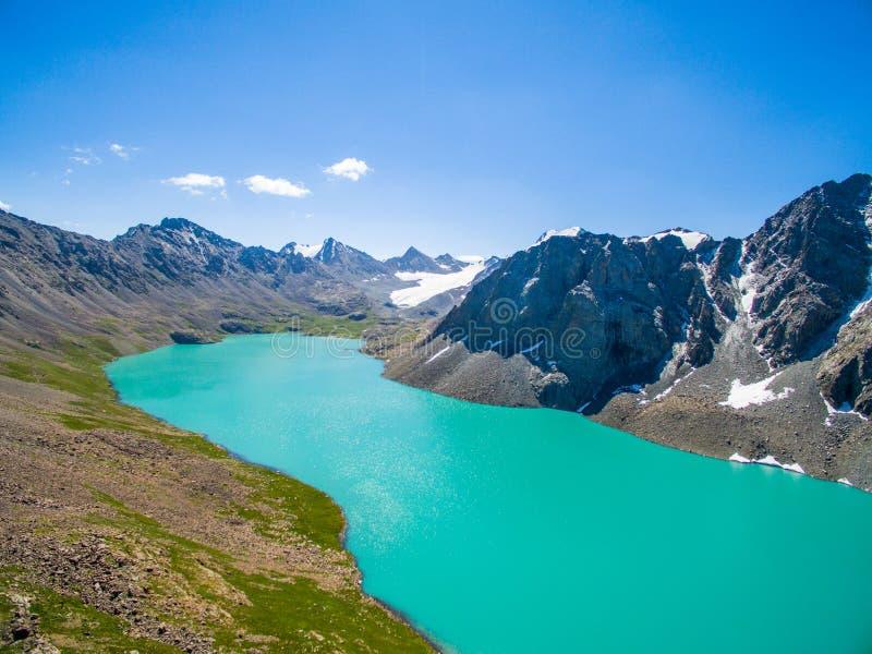 Surrbild från berg sjön med snö- och blåttSkyfrom berg sjön med snö och blå himmel arkivbild
