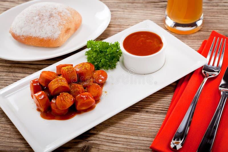 Surre a salsicha picante do wurst com caril e ketchup fotos de stock