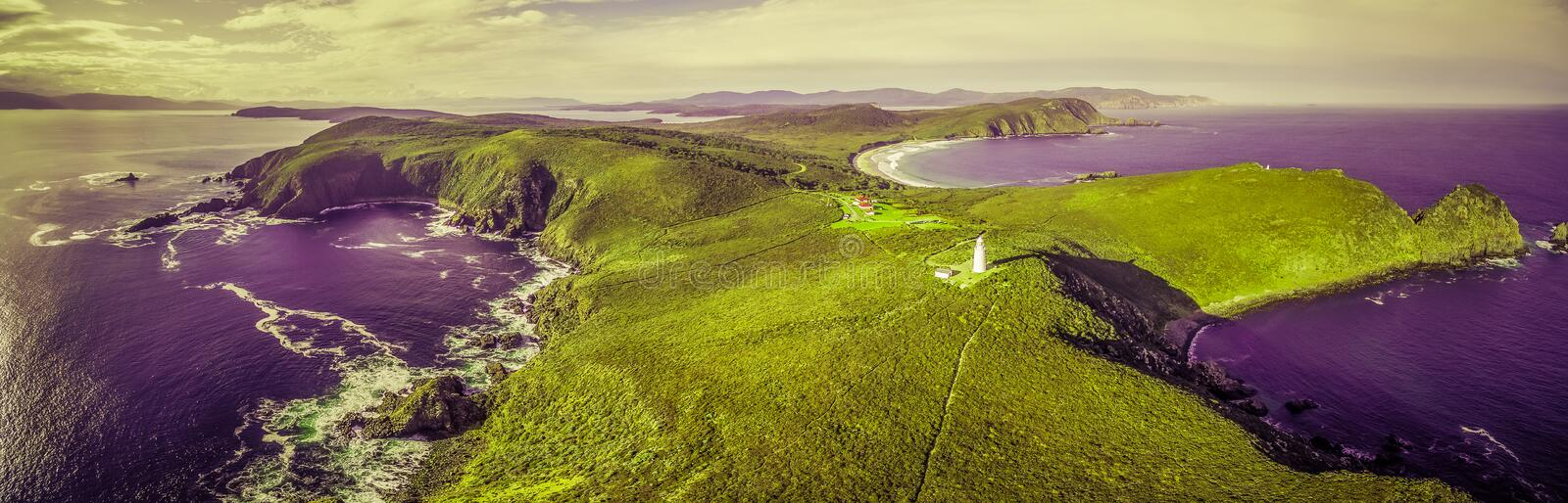 Surreal aerial landscape of ocean, land, and lighthouse stock photo
