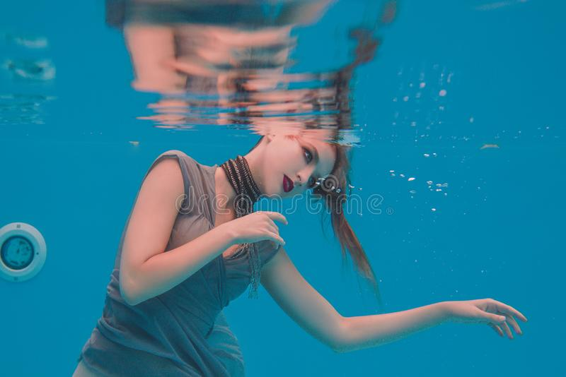 Surreal art portrait of young woman in grey dress and beaded scarf underwater. In the swimming pool royalty free stock images
