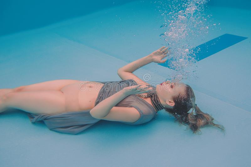 Surreal art portrait of young woman in grey dress and beaded scarf underwater. In the swimming pool royalty free stock photo