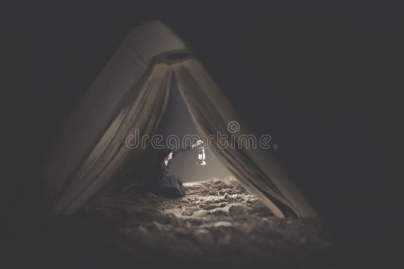 Surreal beeld van een uiterst kleine vrouw die een boek als schuilplaats voor de nacht gebruikt royalty-vrije stock fotografie