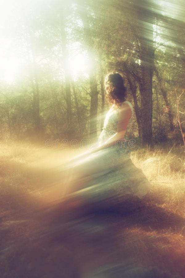 Surreal blurred background of young woman sitting on the stone in forest. royalty free stock photos