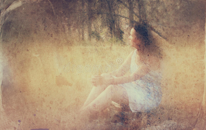 Surreal blurred background of young woman sitting on the stone in forest. abstract and dreamy concept. image is textured and retro royalty free stock image