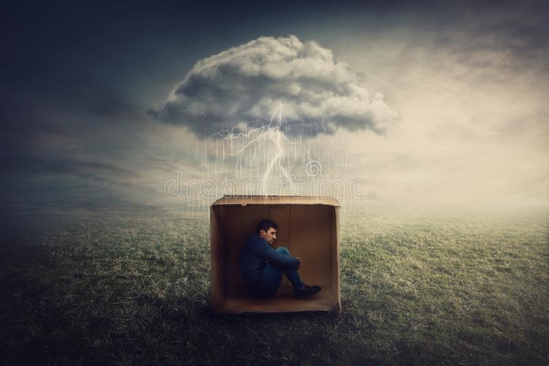 Surreal concept with a scared guy shelters inside a cardboard box. Introvert man caged by own fears as a thunderstorm cloud. Trapped him under the rain stock photography