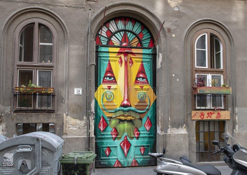 Surreal gezicht op een deur in 12 Kazincy Straat, Boedapest, Hongarije wordt geschilderd dat stock afbeeldingen