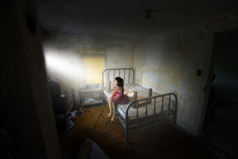 Surreal Girl, Peace, Hope, Love. A young girl sits on a bed in an old house. The child wears a ballerina ballet dancer dress. Surreal scene for peace, hope, love royalty free stock photo