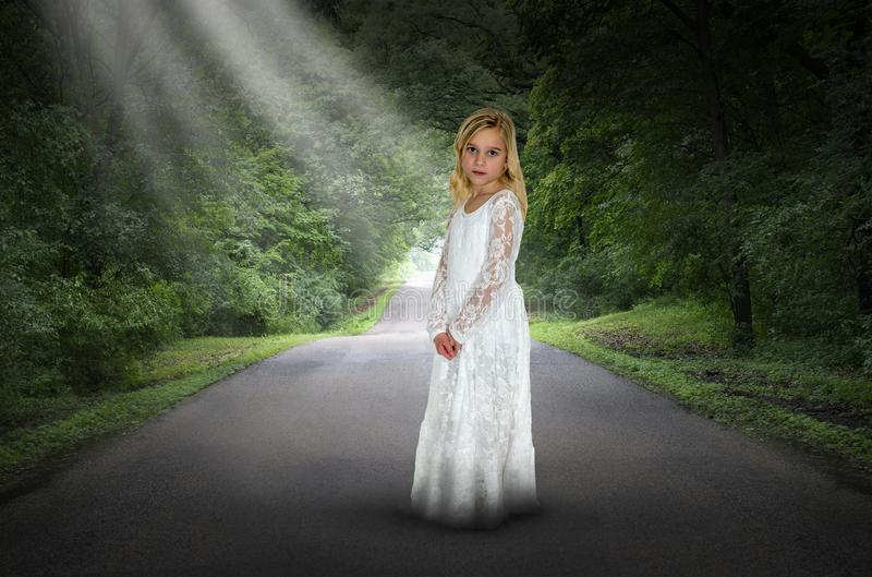 Surreal Girl, Road, Hope, Peace. A young surreal girl child wearing a white dress is in the dark woods and trees on a road or highway. Abstract concept for peace royalty free stock image