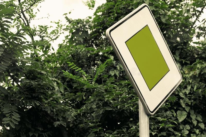Surreal green color traffic sign concept with lush foliage - social issues concept with copy space. Close-up of right of way sign. royalty free stock photo