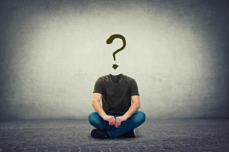 Surreal headless guy, invisible face seated on the floor with a question mark instead of head, like a mask, for hiding identity stock image