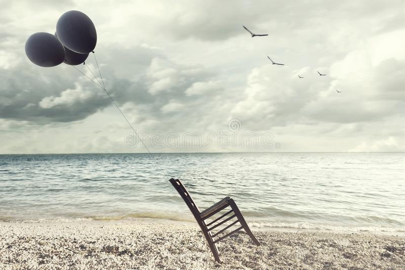 Surreal image of a chair held in balance by flying balloons stock photography
