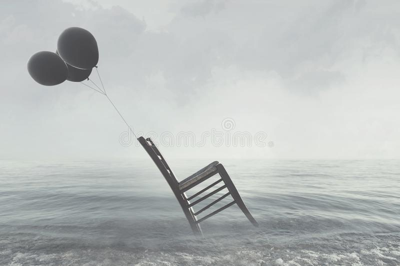 Surreal image of a chair held in balance by flying black balloons stock photography