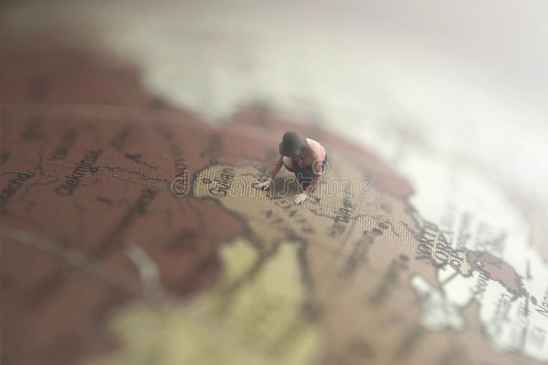 Surreal image of a woman looking for a destination in a giant globe stock photography