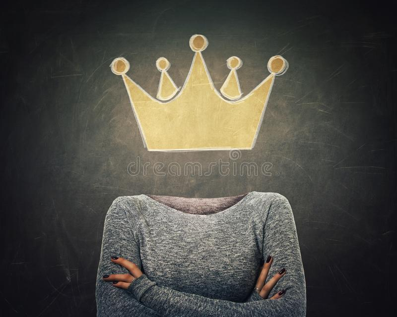 Surreal image young woman with crossed arms and crown symbol instead of head drawn over blackboard background. Business leadership royalty free stock photos