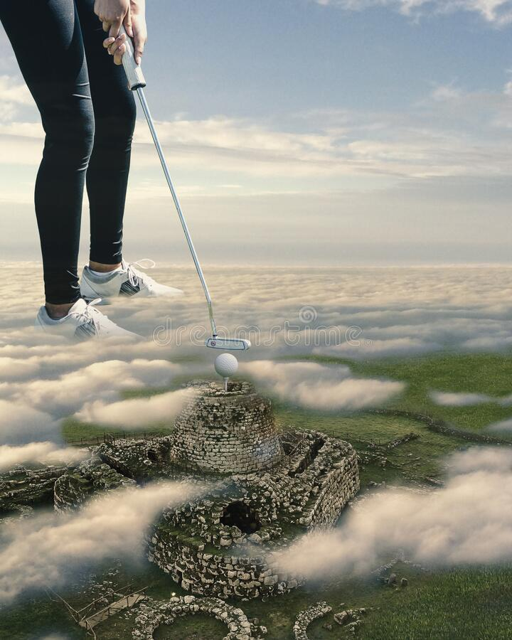 Surreal landscape of Sardinian Nuraghe with young girl playing golf immersed in clouds stock photos