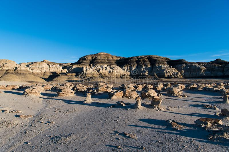 Late afternoon sunlight on an alien landscape of unusual rock formations and boulders in the Bisti Badlands of New Mexico. A surreal landscape of unusual rock stock photos