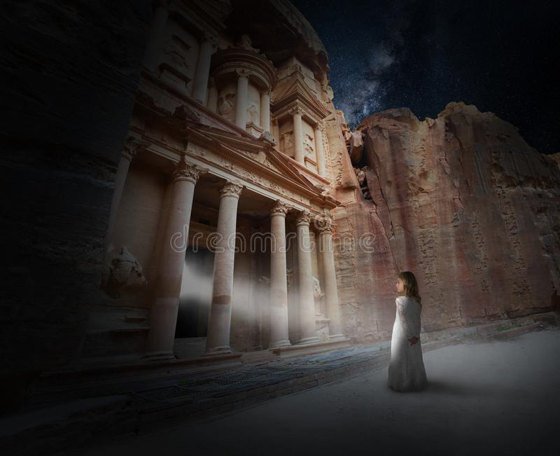 Surreal Magic, Spiritual Rebirth, Fantasy, Science Fiction. A young girl stands in a beam of life of the ancient ruins of Petra in Jordan. Abstract surreal royalty free stock photos