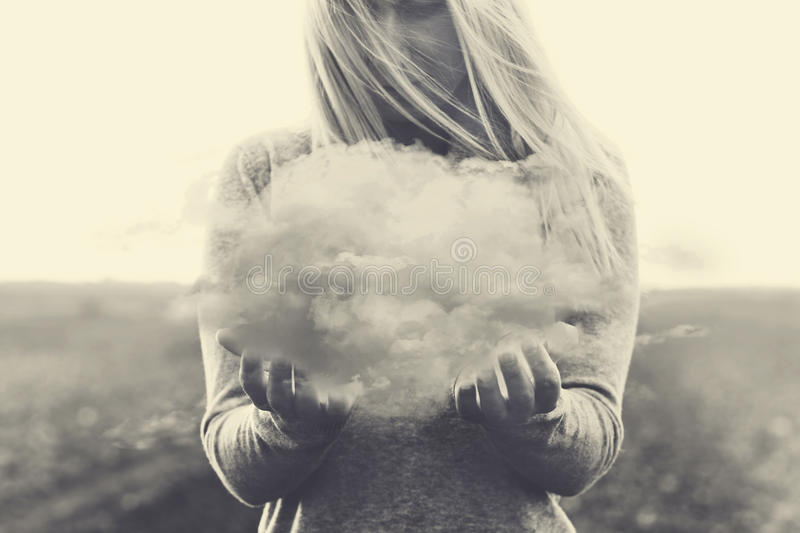 A surreal moment, solitary woman holding in her hands a grey cloud royalty free stock photography