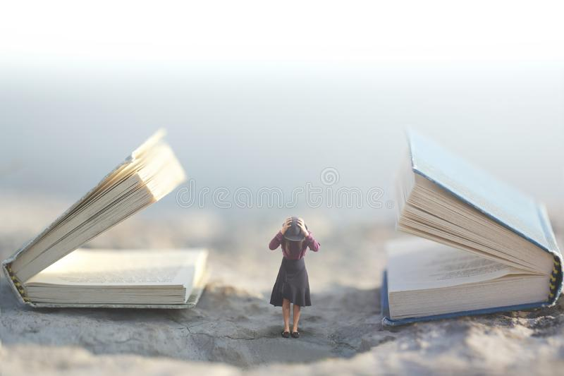 Surreal moment where a small woman stops her ears so as not to listen to two giant talking books. Surreal moment where a small woman stoping her ears so as not royalty free stock images