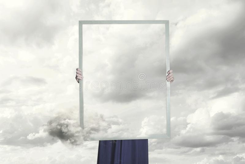 Surreal moment of a woman hiding behind a picture of clouds equal to the landscape stock photos