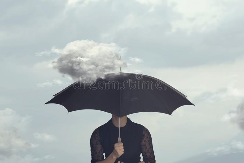 Surreal moment of a woman hiding under the umbrella from a small cloud that chases her royalty free stock images