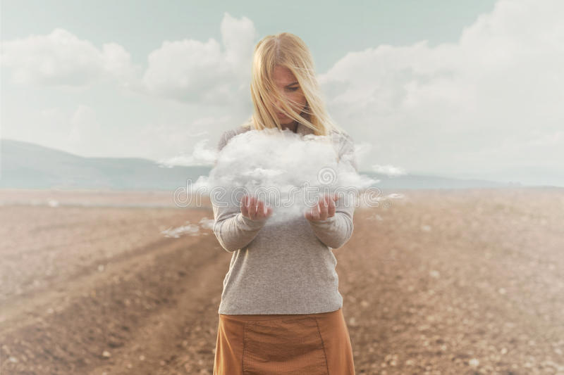 Surreal moment of a woman holding a cloud in her hands royalty free stock photo