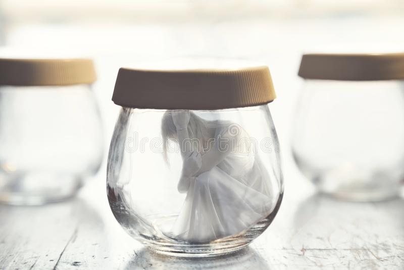 Surreal moment of a woman inside a glass jar stock photos
