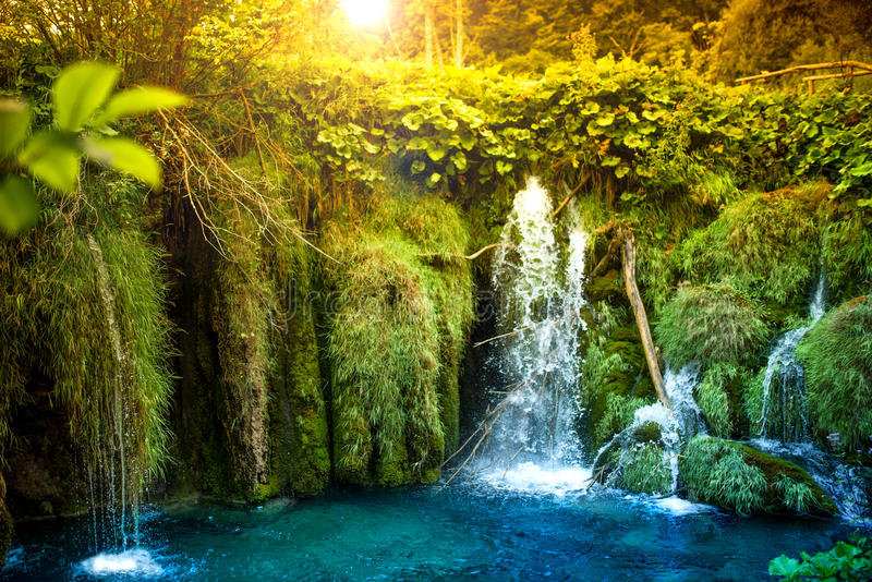 Surreal natural lake waterfall with blue, turquoise water and tropical forest royalty free stock photos
