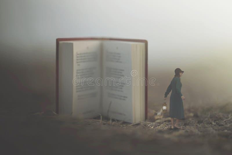 Surreal ogenblik van een vrouw met lantaarn lopen verward in de mist tussen reuzeboeken stock foto