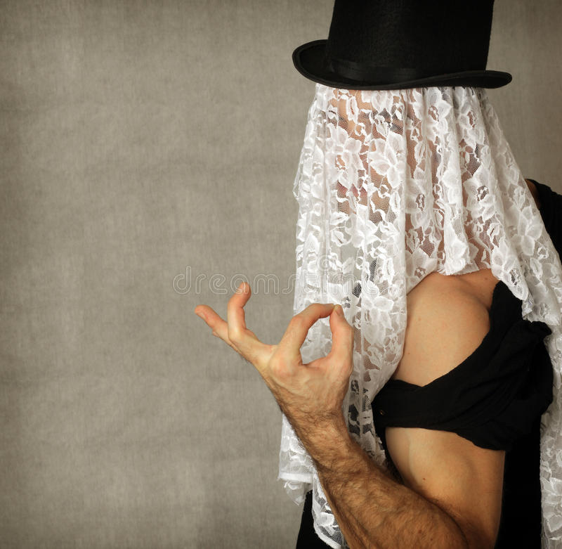 Surreal portrait. Fantastical stylized portrait of mystery man making a hand gesture in top hat with lace covering his face royalty free stock photography