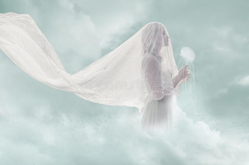 Surreal portrait of bride in clouds hold jellyfish stock photo