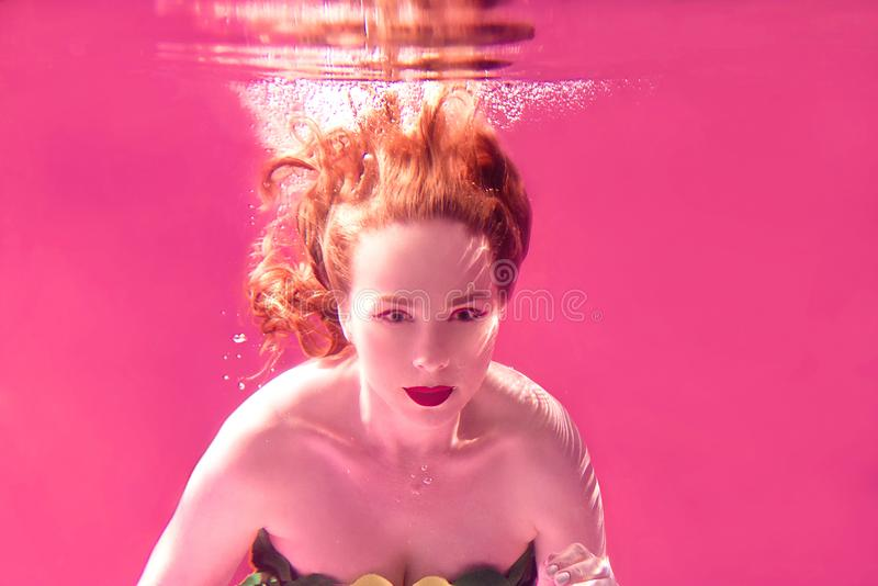 Surreal portrait of young attractive woman underwater in colorful water stock image