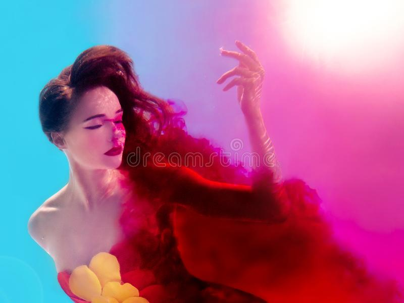Surreal portrait of young attractive woman with air bubbles underwater in colorful water with ink royalty free stock photos