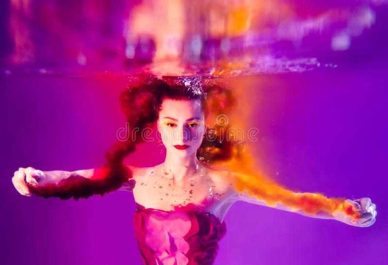 Surreal portrait of young attractive woman underwater in colorful water stock photo