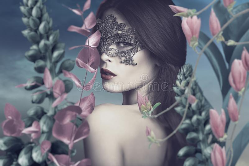 Surreal portrait of young woman with lace mask in fantasy garden royalty free stock images