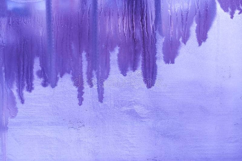Surreal purple winter frozen window glass with vertical melted bands and copy space. Surreal purple winter frozen window glass pane with vertical melted bands royalty free stock image