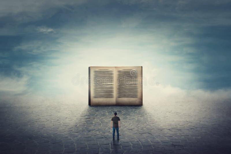 Surreal scène als studentenkerel bevindt zich op een bestratingsweg voor een reuze geopend boek Het belang van lezing en literatu royalty-vrije stock foto's