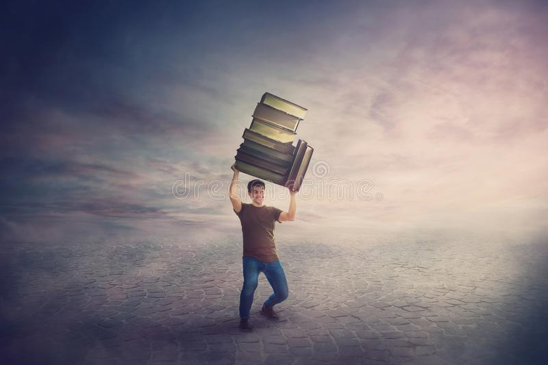 Surreal scene, angry student guy tired of constant learning, carrying huge heavy books pile over his head. Frustrated boy back to royalty free stock photography