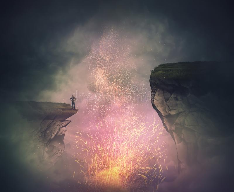 Surreal scene as a fearless man stand on the edge of a cliff watching the magical fire sparkles eruption as from a volcano crater stock photo