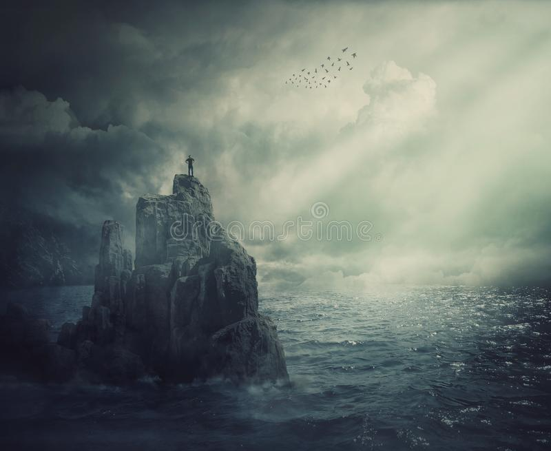 Surreal scene as man silhouette standing on the top of a cliff surrounded by the sea water. Meditation metaphor, conquering. Adversity and overcoming challenges royalty free stock images