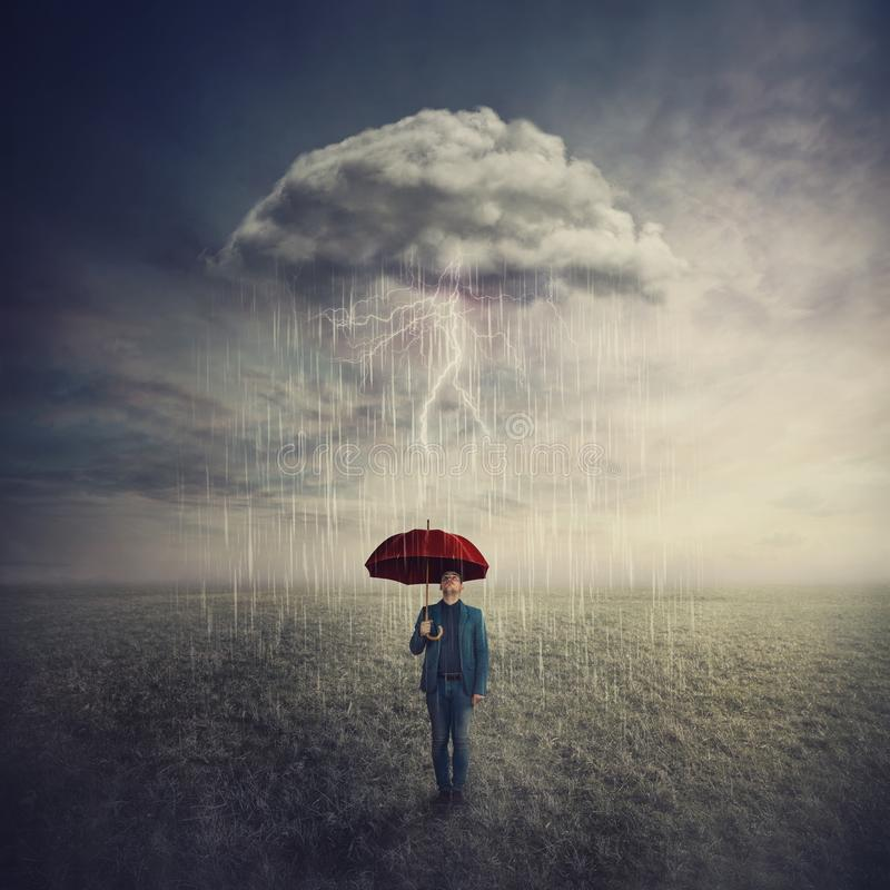 Surreal scene as man stands outdoors under umbrella due a single mysterious storm cloud raining only over him. Find solution to stock photography