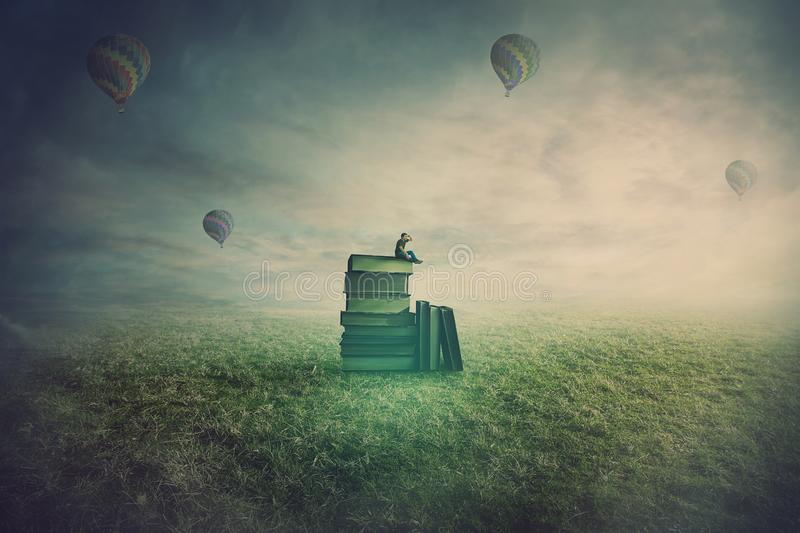 Surreal scene as a minuscule man seated on the top of a books pile in a open foggy field, holding hand to forehead looking at the stock image