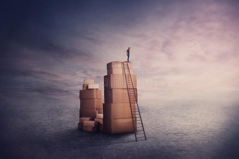 Surreal scene as a minuscule man wanderer standing on a stack of cardboard boxes, holding hand to forehead looking at the horizon royalty free stock photo