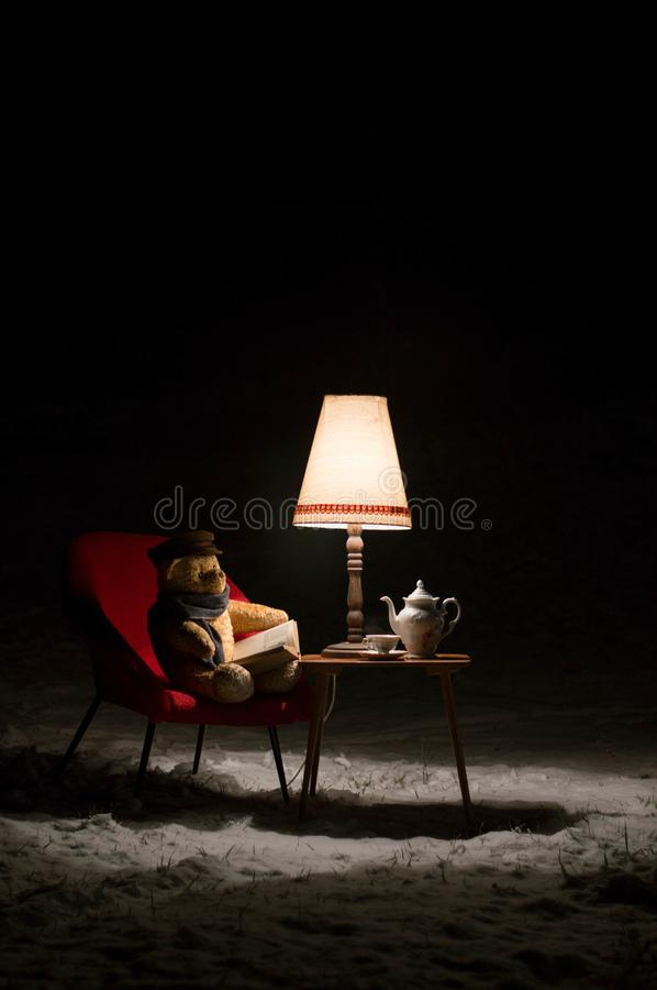 Teddy bear read a book outside in a winter night - surreal scene royalty free stock photo