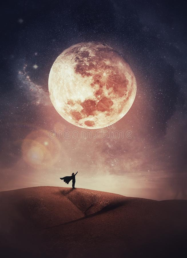 Free Surreal Scene With A Woman Hero Silhouette With Cape On The Top Of A Hill Raises Hand Up To The Sky Watching The Full Moon Night. Stock Photos - 162264973