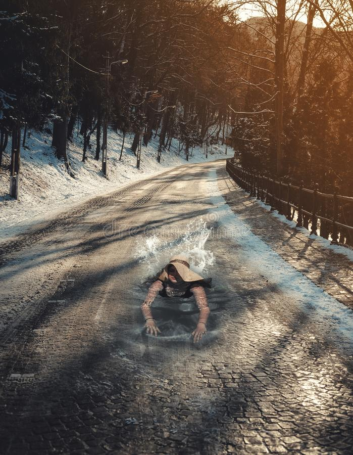 Surreal swimming in a winter road stock photo